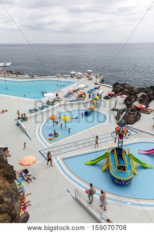 FUNCHAL, MADEIRA, PORTUGAL - SEPTEMBER 3, 2016: Swimming pool with tourists at Lido hotels zone in Funchal Madeira island Portugal