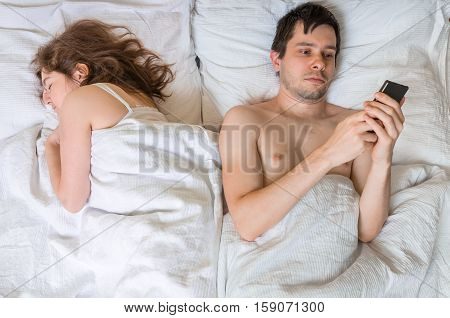 Young Man Is Texting With Someone Using Phone While His Wife Is