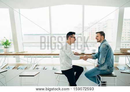 Men Are Sitting At Table In Modern Cafe