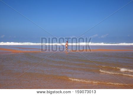 LIENCRES DUNES SPAIN - AUGUST 21: Woman walking in the water edge of the Liencres dunes nature reserve in the Cantabrian sea on August 21 2016