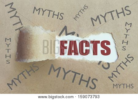 Torn brown paper revealing the word facts surrounded by myths
