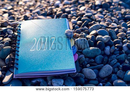 Paper notebook with text 2017 lying at on sea beach. Closeup. New year waiting. Planning and writing goals. Making strategy for new year 2017.