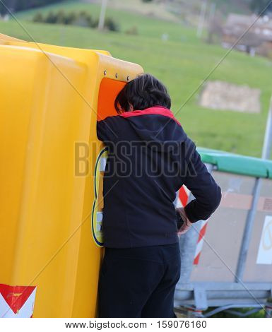 poor young boy looks into the yellow garbage can in search of something