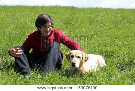 smiling boy on the meadow in the mountains with his yellow Labrador Retriever dog