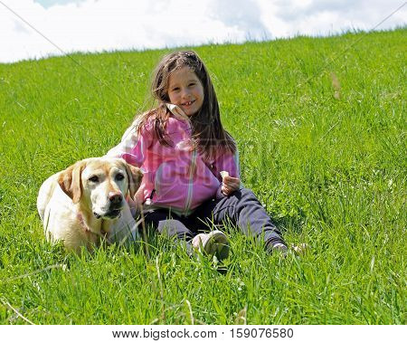 Young Girl Smiling On The Grass In The Mountains With Her Labrad