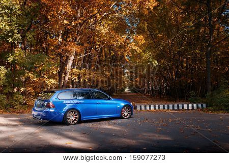 Moscow, Russia - October 02, 2016: Blue car BMW 3 Series E91 standing near autumn park forest