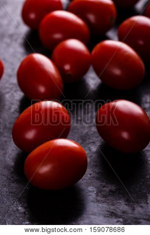Several Cherry Tomatoes On Black Board