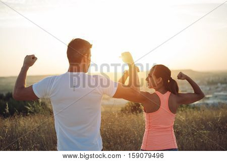 Couple Of Runners Lexing Biceps Towards The Sun
