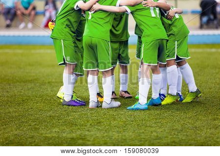Young football soccer players in green sportswear. Young sports team on pitch. Pep talk before the final match. Soccer school tournament. Children on sports field.
