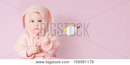 Closeup portrait of cute baby with blue eyes in knitted costume of Easter rabbit on pink background with copyspace for your text. Poster for Easter holiday. Easter bunny.