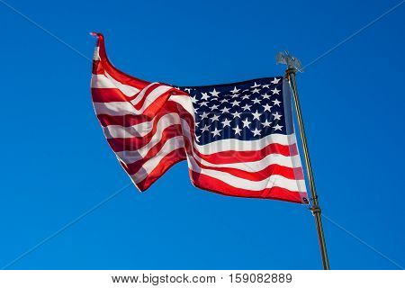 Star spangled banner in the wind with blue sky.