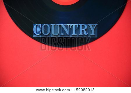 The word country in metal type on a black vinyl record on a red background with copy space