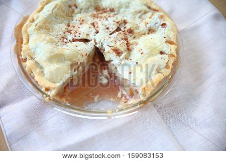 Overhead view of homemade apple pie sprinkled with cinnamon with copy space