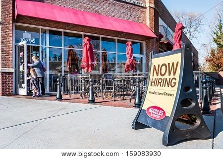 Fairfax, USA - November 27, 2016: Noodles & Company World Kitchen outdoor seating area with Now Hiring sign