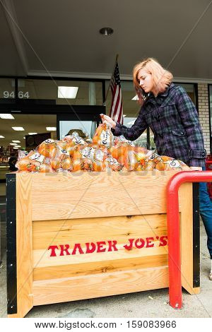 Fairfax, USA - November 25, 2016: Woman picking oranges from Trader Joes grocery store by entrance