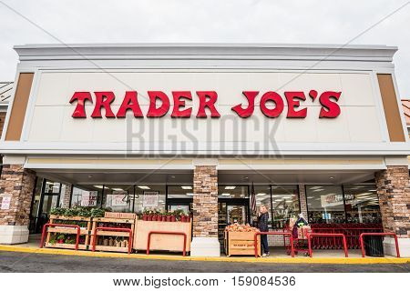 Fairfax, USA - November 25, 2016: Trader Joes grocery store facade with sign and items on display and people walking