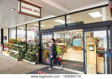 Fairfax, USA - November 25, 2016: Trader Joes grocery store entrance with sign, display and view on interior with woman walking out