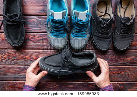 man chooses shoes holding black loafers close up