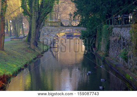 The photograph shows a historic stone bridge. It is passed over a small river, and is part of the architectural palace in the city Iłowa in western Poland.