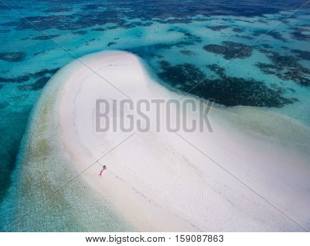Tiny mermaid lying on white sandy beach of a Maldives peninsula, turquoise ocean around, drone aerial view. Woman wearing mermaid fancy dress seen from above.