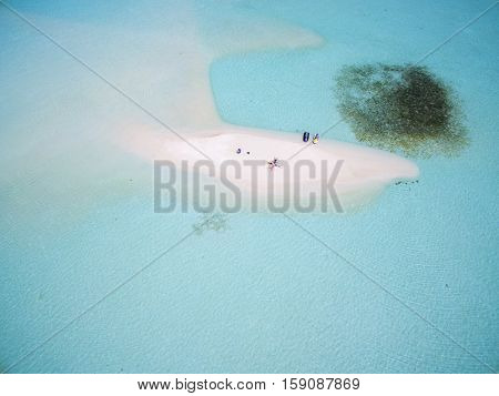 We are lying down on Maldives Island Indian Ocean sandbank, top aerial view. Turquoise water white sandy beach. Travel summer holiday drone selfie concept