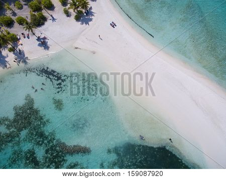Landscape seascape aerial view over a Maldives Male Atoll island. White sandy beach and tiny people seen from above.