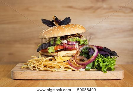A delicious burger with two cutlets basil thin fries lettuce and onion rings on a wooden board. Photo causing appetite. The concept of fast food delicious but unwholesome food.
