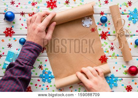 Man Holding A Wishlist On The Background Of Snowflakes