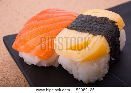 Sushi salmon shrimp eggs Tamagoyaki Ebiko Ebi Nigiri This is surrounded by Maki Sushi and pages. Focus salmon. Blurred background there are some points not in focus.