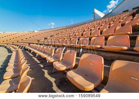 Empty seats at soccer stadium on blue sky.