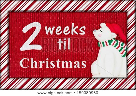 Christmas countdown message Red shiny fabric with a candy cane border and a Santa polar bear with text 2 weeks til Christmas 3D Illustration
