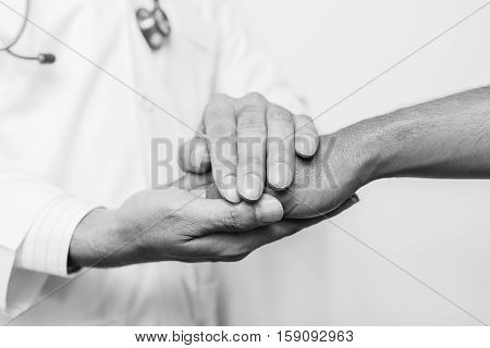 Two people holding hands for comfort black and white.doctor's hands holding patient's hand for encouragement and empathy. Doctor concept. Doctor man. Doctor support. Doctor talk. Doctor trust. Doctor shake. Doctor waiting
