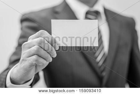 Man's hand showing business card - closeup sho black and white. Business man. Card in hand business. Business room. Business office. Business using card.