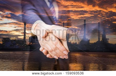 Double exposure of handshake and refinery. handshake on refinery background. refinery on sunrise. Business handshake and business people. Shake hands after their meeting. man handshake. Business concept. Business working.