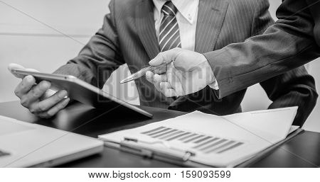 Image of two young businessmen using tablet at meeting black and white. Business working. Business room. Business man. Business woman. Business using taplet. Business using internet.