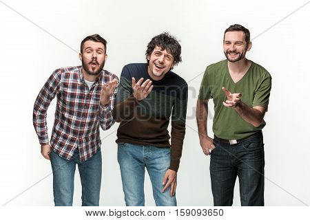 The young three men are smiling, looking at camera, standing on white studio background with different emotions