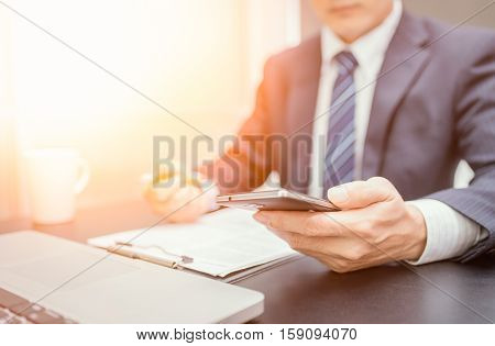 Businessman hand using mobile phone on sunset. Business looking smartphone. Business playing smartphone. Business using smartphone. Uniform business. Business room. Business using mobile. Business using internet.
