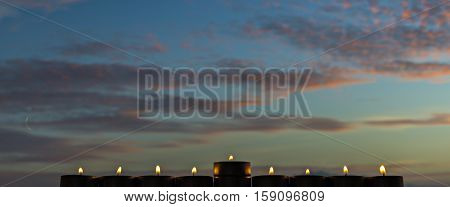 Silhouette of menorah (traditional candelabra for Hebrew Holiday against the colorful background of cloudscape at sunrise, selective focus applied