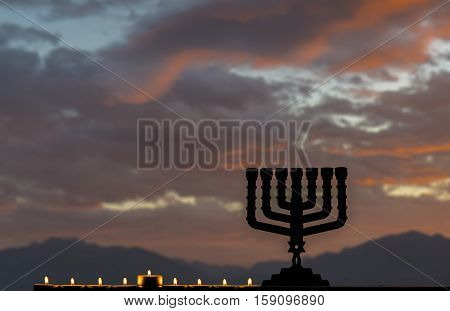 Menorah with the glitter lights of candles is traditional Jewish symbol for Hanukkah holiday. Selective focus. Mountains and cloudscape as background