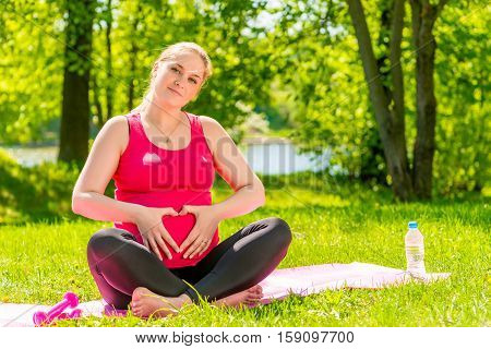 Beautiful Pregnant Woman Showing Heart Symbol Hands Near The Abdomen