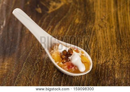 Fruit Salad With Meringue And Coffee Sago In A Spoon. Taste Gastronomy Finger Food