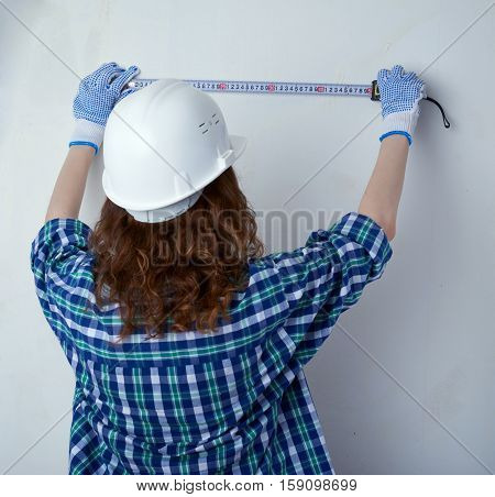 Young woman in casual clothes in front of white unpainted wall in white helmet working with measuring tape, happy people and construction concept