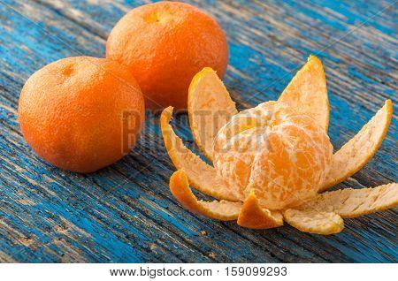 mandarines, peeled tangerine and tangerine slices on a blue wooden table