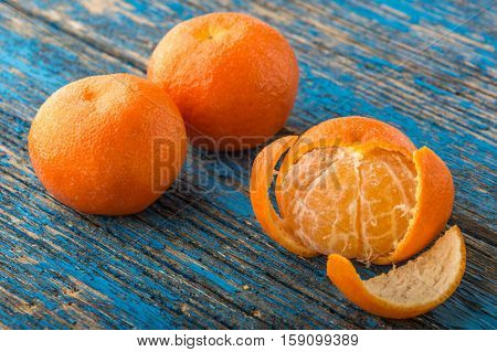 mandarines, peeled tangerine and tangerine slices on a blue wooden table