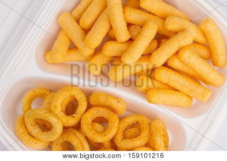 top view close up of potato and corn junk food ingredients in a white take away packaging box on yellow background calories concept