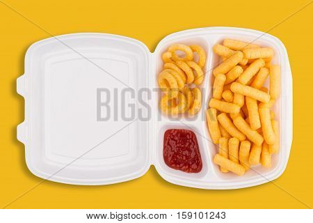 top view of junk food ingredients and a dip of ketchup in a white take away packaging box on yellow background calories concept