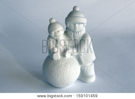 Porcelain figurine depicts children who make a snowman. Serial porcelain from the decor store