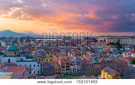 Sunset on Cagliari, panorama of the old city center with traditional colored houses, mountains and beautiful yellow-pink clouds in the sky, Sardinia Island, Italy