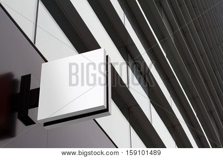 Horizontal side view of empty white signage on business skyscraper with modern architecture and glass windows