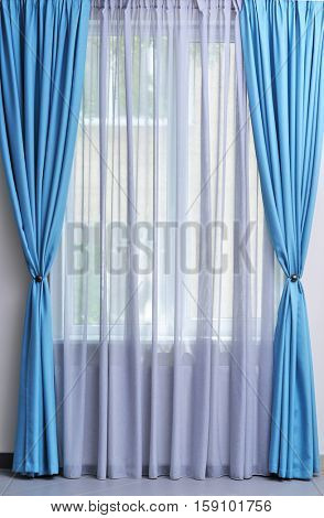 Room window with white and blue curtains